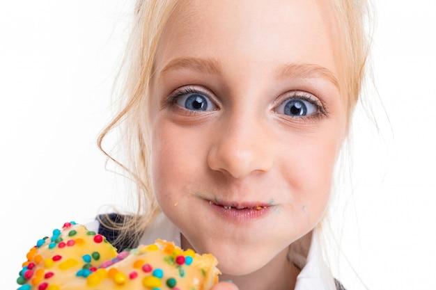 馬の尾、大きな青い目、かわいい顔を詰めたブロンドの髪を持つ少女は、釉薬で覆われた明るいドーナツを食べる Premium写真