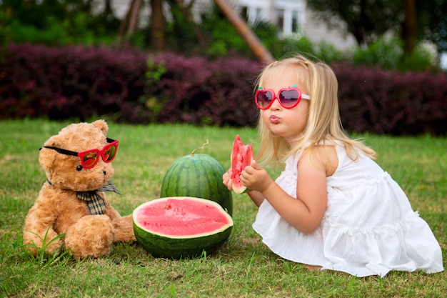 Little girl with blonde hair in sunglasses eating watermelon on the park, next sitting teddy bear Premium Photo