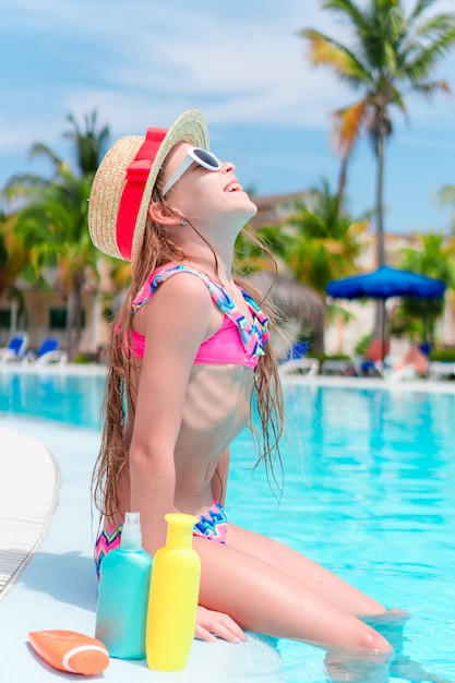 Little girl with bottle of sun cream sitting on the edge of swimming pool Premium Photo