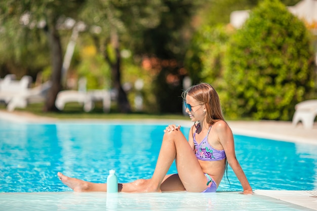 Little girl with bottle of sun cream sitting at tropical beach Premium Photo