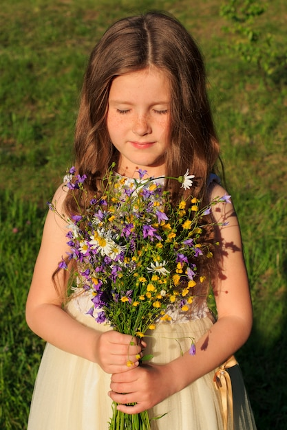 Little girl with a bouquet of wildflowers and eyes closed Premium Photo