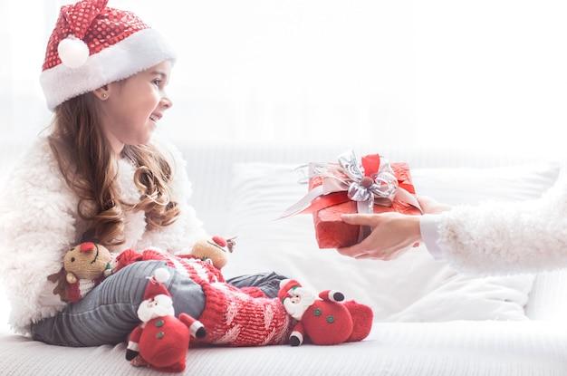 Маленькая девочка с рождественским подарком в костюме санты Premium Фотографии