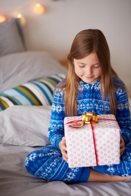 ベッドでクリスマスプレゼントの少女 無料写真
