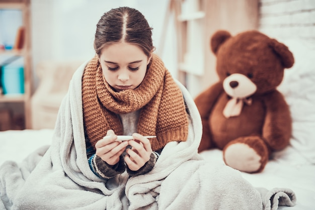 Little girl with cold in scarf and blanket with thermometer. Premium Photo