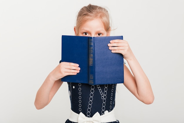 Little girl with face behind book Free Photo