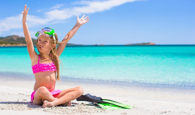 Little girl with flippers and goggles for ssnorkling on the beach Premium Photo