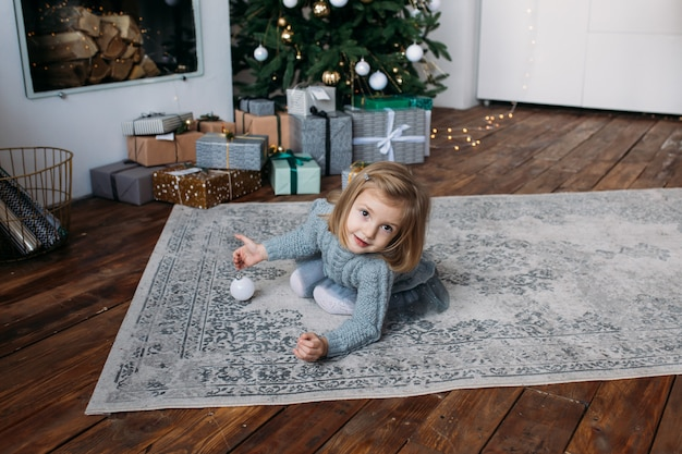 Little girl with gift boxes and christmas tree on background Premium Photo