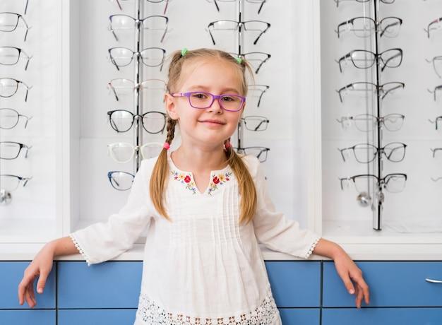Маленькая девочка в очках, стоя в оптическом магазине Premium Фотографии