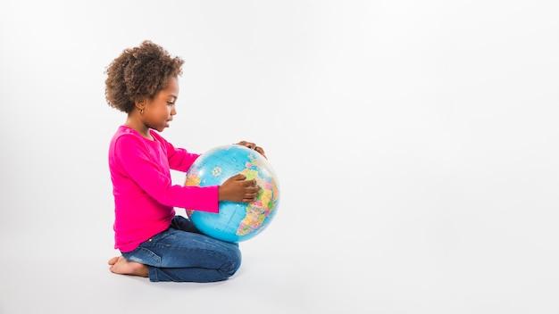 Little girl with globe in studio Premium Photo