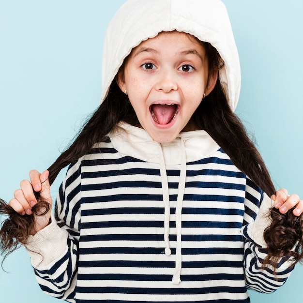 Little girl with hoodie playing with hair Free Photo