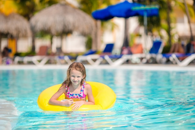 Little girl with inflatable rubber circle having fun in outdoor swimming pool in luxury hotel Premium Photo