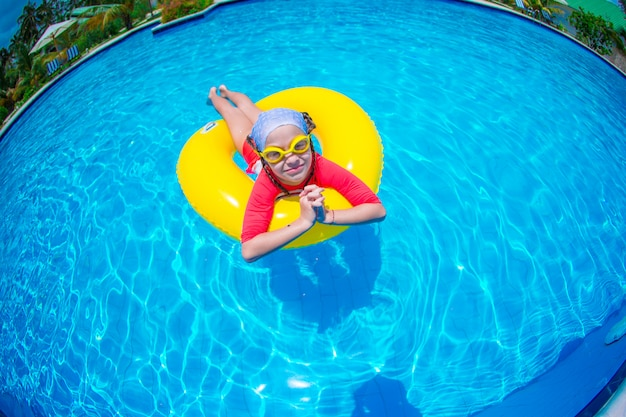 Little girl with inflatable rubber circle having fun in swimming pool Premium Photo