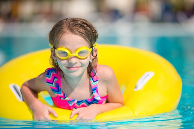 Little girl with inflatable rubber circle in swimming pool Premium Photo