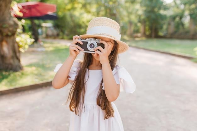 Bambina con capelli scuri lunghi che tiene la macchina fotografica nelle mani in piedi sul vicolo nel parco. bambino femminile in cappello di paglia con nastro bianco che cattura foto della vista della natura in una giornata di sole. Foto Gratuite