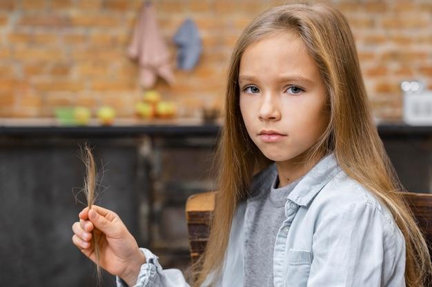 彼女が美容院で切ったものを保持している長い髪の少女 Premium写真