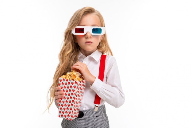 A little girl with makeup and long blonde hair with pop-corn and 3d glasses Premium Photo