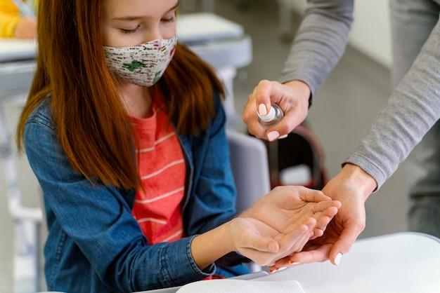 선생님에게서 손 소독제를 받고 의료 마스크와 어린 소녀 무료 사진