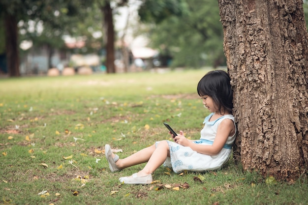 Little girl with a mobile phone in the park Premium Photo