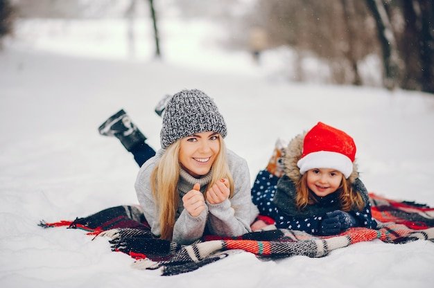 Little girl with mother playing in a winter park Free Photo