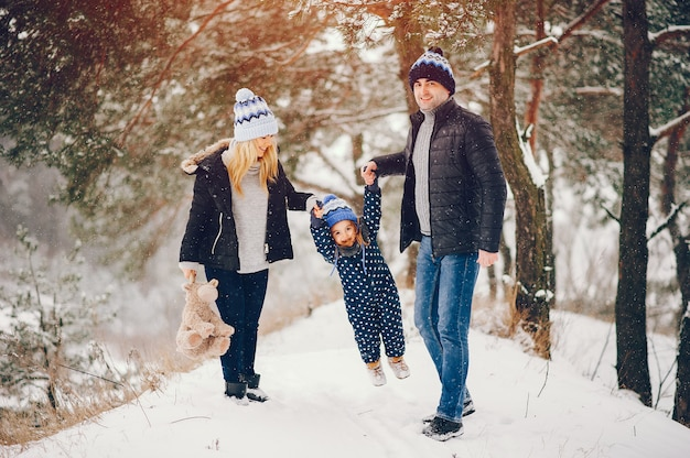 Little girl with parents playing in a winter park Free Photo