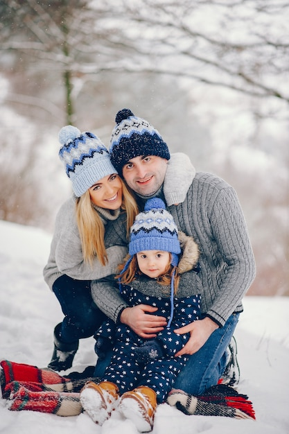Little girl with parents sitting on a blanket in a winter park Free Photo