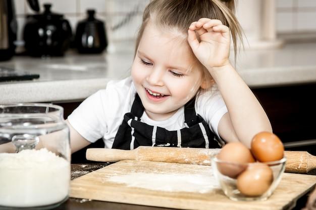 Little girl with  preparing bake homemade holiday pie in kitchen. Premium Photo