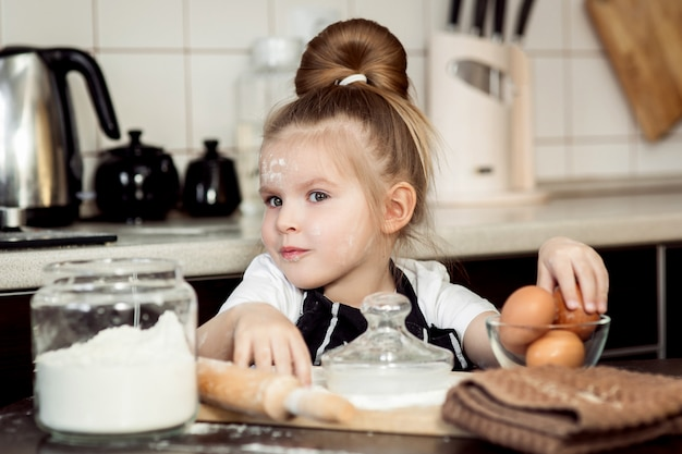 Little girl with  preparing bake homemade holiday pie in kitchen. Premium Photo
