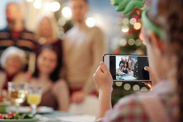 Маленькая девочка со смартфоном фотографирует большую счастливую семью, собравшуюся за сервированным столом на рождественский ужин дома Premium Фотографии