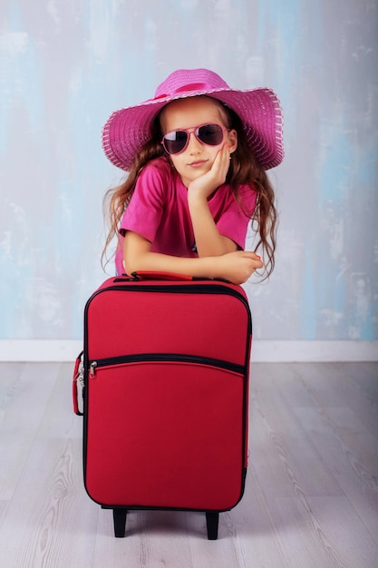 The little girl with a suitcase. the concept of travel and leisure. Premium Photo