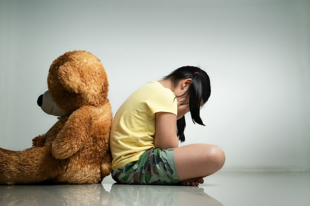 Little girl with teddy bear sitting on floor at empty room. mental and depressed family concept. back view Premium Photo