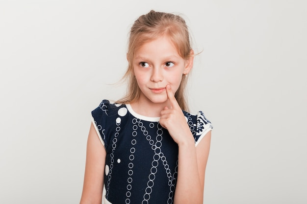 Little girl with thinking expression Free Photo