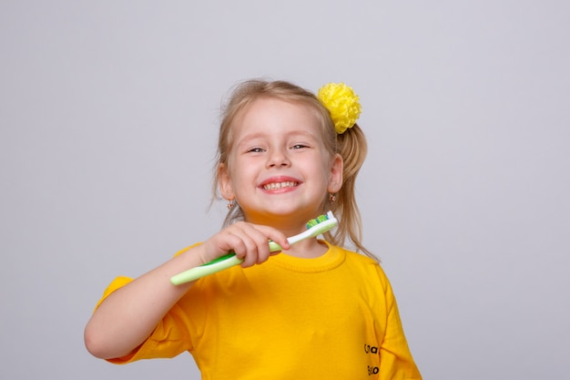 Little girl with a toothbrush, little girl with a toothbrush and an apple. Premium Photo