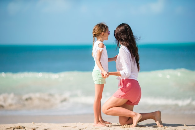 Little girl and young mother on beach vacation Premium Photo