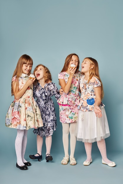 Little girls have fun and play, celebrate their birthday, eat cakes and blow bubbles. girls in beautiful dresses on a blue background pose and have fun. Premium Photo
