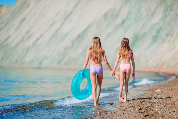 Маленькие девочки веселятся на тропическом пляже, играя вместе Premium Фотографии