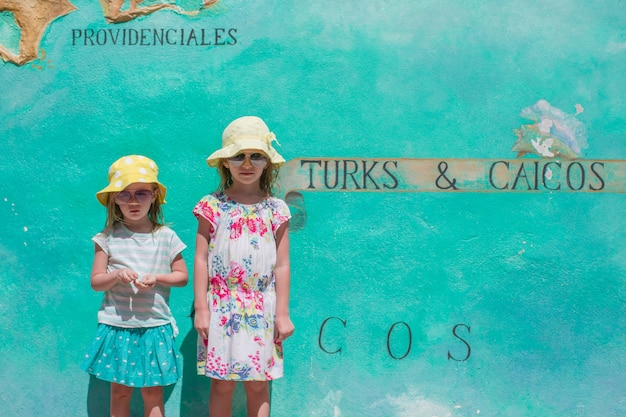 Little girls near big map of caribbean island turks and caicos painted on the wall Premium Photo