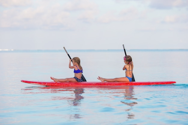Little girls swimming on surfboard during summer vacation Premium Photo
