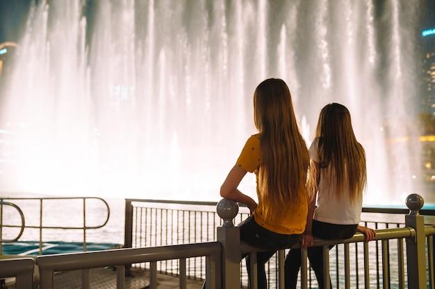 Little girls watch the legendary show of singing fountains in dubai Premium Photo