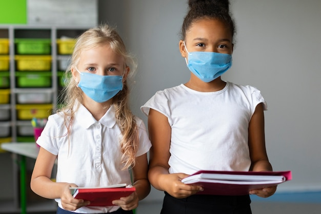 Маленькие девочки в медицинских масках в классе Бесплатные Фотографии