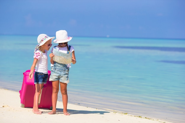 Little girls with big suitcase and map at tropical beach Premium Photo