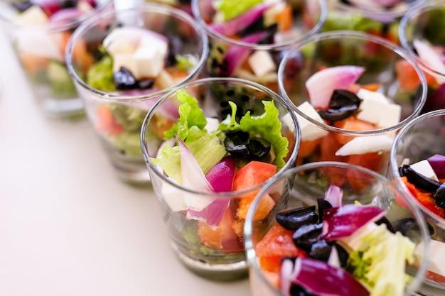 新鮮なサラダ、卵、サーモン、きゅうりの白いテーブルの上に立って小さなグラス Premium写真