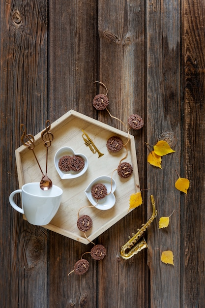 Little golden saxophone and autumn leaves and a tray with cup and cookie. autumn Premium Photo