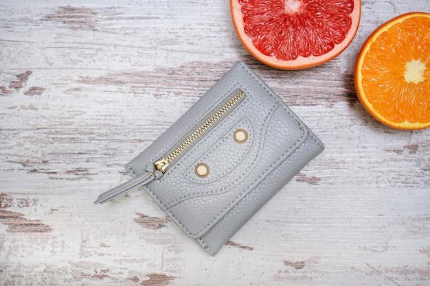 Маленькая серая женская сумочка и цитрус на свитере. модная концепция. Premium Фотографии