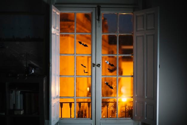 Little halloween paper bats on window in room Free Photo