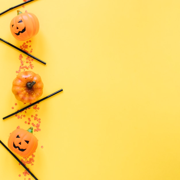 Little halloween pumpkins and plastic tubes laid in line Free Photo