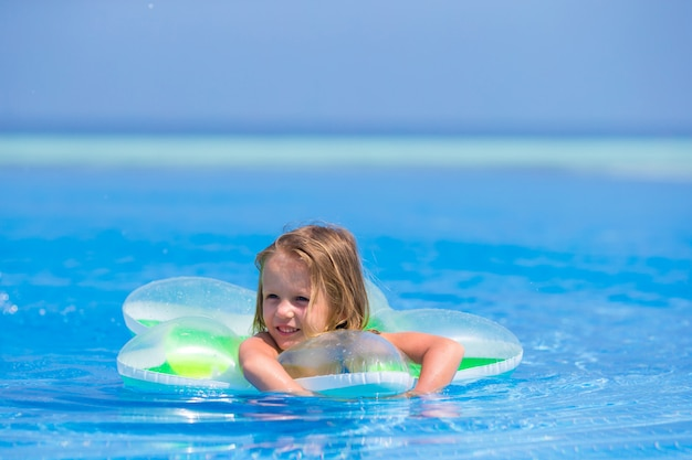Little happy adorable girl in outdoor swimming pool Premium Photo