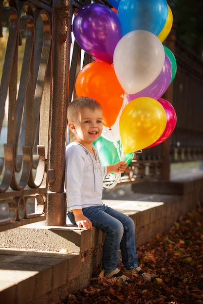 Little happy boy with colorful balloons outdoor in summer. Premium Photo