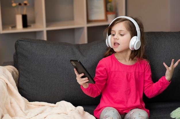自宅のヘッドフォンで音楽を聴きながらソファーで踊る幸せな少女。ヘッドフォンを着て踊ったり、歌ったり、リズムに移ったりする女の子 Premium写真