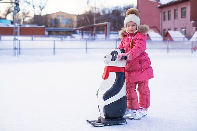 Little happy girl learning to skate on the rink Premium Photo