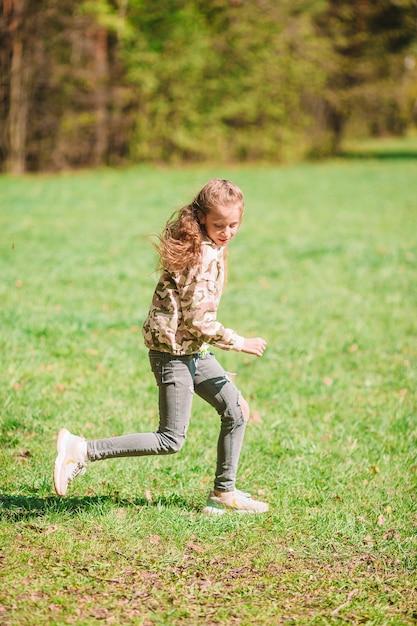 Маленькая счастливая девочка на открытом воздухе в парке работает и веселится Premium Фотографии